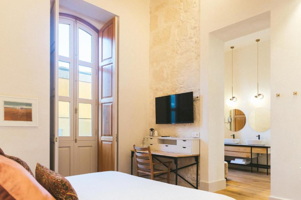 Una televisión o centro de entretenimiento en VEINTIUNO Emblematic Hotels - Adults Only