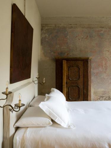 Una cama o camas en una habitación de Palazzo Albricci Peregrini