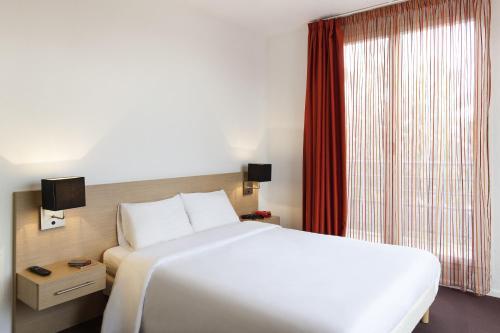 Cama ou camas em um quarto em Aparthotel Adagio Access Saint Louis Bâle